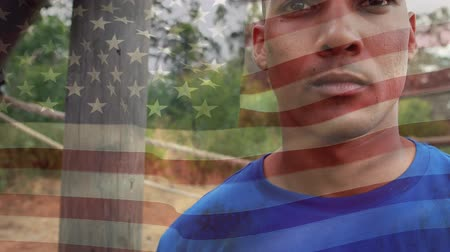 строгий : Digital composite of an African-american man with a serious expression and an obstacle course behind him. American flag is waving in the foreground