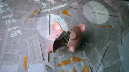 돼지 저금통 : Digital composite of breaking a piggy bank on a pile of newspapers with graphs and statistics running in the foreground