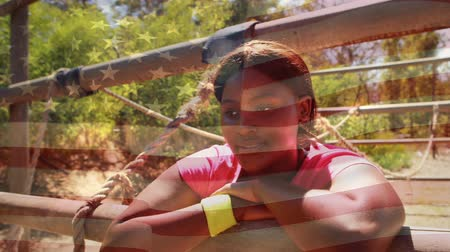 kurs : Digital composite of an African-american woman resting after completing a rope cross with an American flag waving in the foreground. Behind her is another person approaching the rope cross