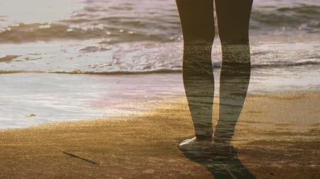 acalmar : Digital composite of a woman standing barefoot on the beach at sunset