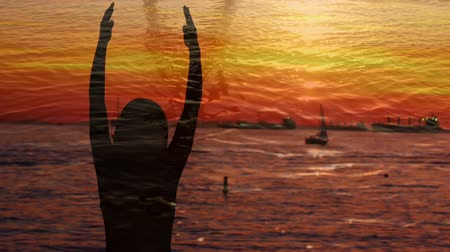 acalmar : Digital composite of silhouette of a woman doing yoga near a port at sunset Stock Footage