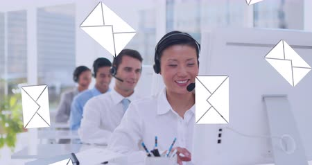 spam : Digital composite of an Asian female call centre agent typing while talking on a headset with message icons flying in the foreground. Behind her are her fellow call centre agents 4k