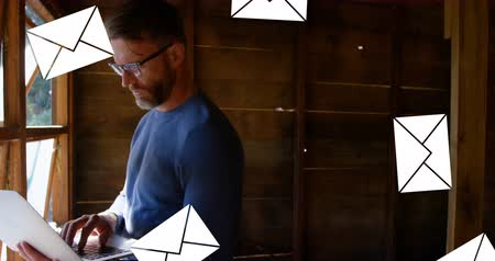 poddasze : Digital composite of a Caucasian man in the attic typing on a laptop with message icons flying in the foreground 4k Wideo