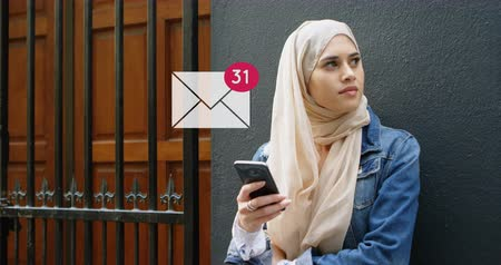 arayüz : Digital composite of a Muslim woman leaning on a wall near the door while texting with a message icon increasing in count in the foreground 4k