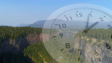 timeline : Digital composite of a wide view of mountains filled with trees and clock running in the foreground Stock Footage
