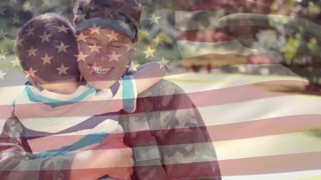 hizmet etmek : Digital composite of an American female soldier giving his son a big hug in the park with an American flag waving in the foreground