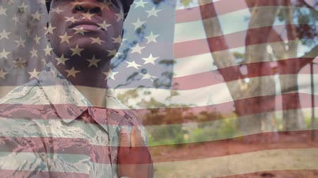 marş : Digital composite of an African american soldier with his hand on his chest with a flag waving in the foreground