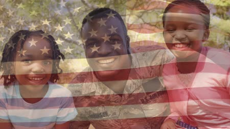 ailelerin : Digital composite of an African american soldier smiling with his two daughters in the park with an American flag waving in the foreground