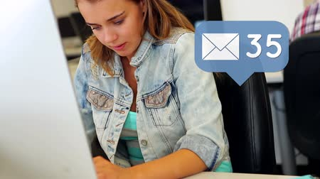 spam : Digital composite of a female Caucasian teen typing on a laptop on a desk with a message icon increasing in count in the foreground Stock Footage