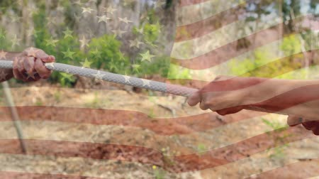 pulling rope : Digital composite of two people pulling on a rope against each other in a boot camp with an American flag waving in the foreground Stock Footage
