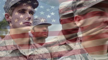 хмурый : Digital composite of American soldiers with serious faces standing at attention with an American flag waving in the foreground