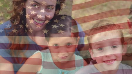 old glory : Digital composite of an American soldier with his wife and two kids in the park with an American flag waving in the foreground