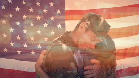 saluto militare : Digital composite of a Caucasian man in military uniform hugging a Caucasian woman while foreground shows an American flag