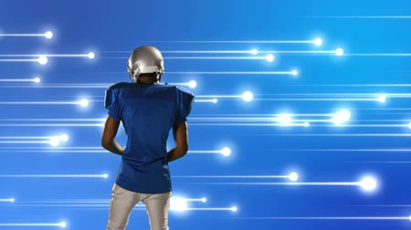 keresztül : Digital composite of an African-American football player holding football with a background of glowing lines moving across the screen