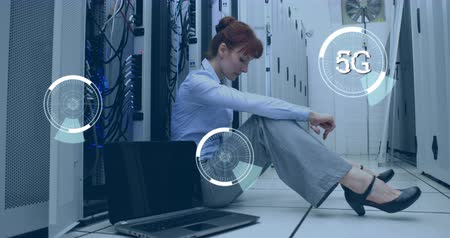 adminisztrátor : Digital composite of a Caucasian woman sitting beside a laptop in a corridor of server towers while futuristic circles with 5G moving on the screen 4k