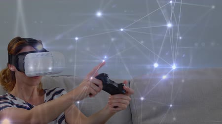 összekapcsol : Digital composite of a Caucasian woman wearing virtual goggles while playing and glowing asymmetrical lines move in the screen