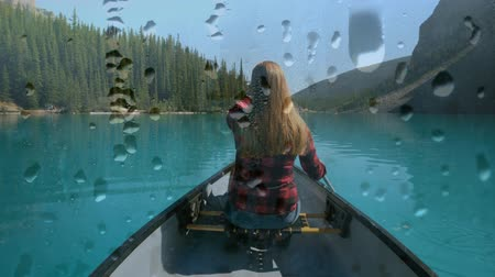 гребля : Digital composite of a Caucasian woman boating in a lake with water droplets in a glass