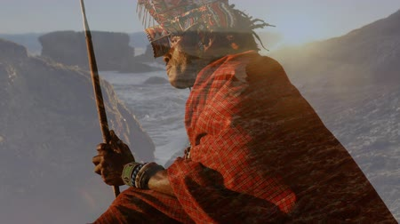 nativo americano : Digital composite of a Native American man holding a stick while sitting on a rock with background of the ocean during sunset Vídeos
