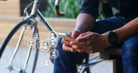 tárcsázás : Low angle view of a man using a mobile phone with a bicycle on his right. Several vector icons of people appearing near the phone. 4k