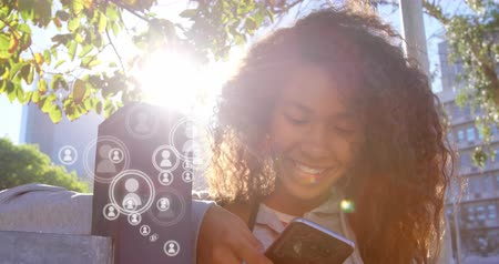 representação : Close-up view of young African American woman in university who is smiling while using her phone. Several vector icons of people appearing near the phone. 4k Vídeos
