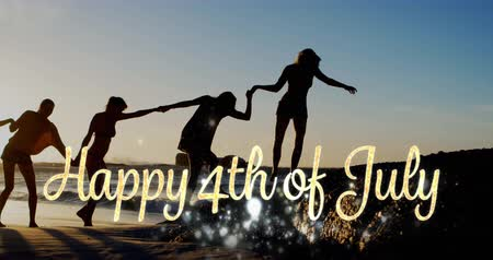 társ : Digital composite of silhouette of diverse friends holding hands while walking by the beach during sunset and a gold Happy 4th of July greeting with shiny lights appear in the foreground 4k Stock mozgókép