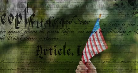 anayasa : Digital animation of written constitution of the United States moving in the screen while hand holds out American flag in park. 4k
