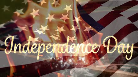 escrito : Digital animation of gold Independence Day text appears in the screen while fire burns and American flag waves in the background. Vídeos