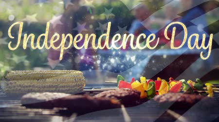 yazılı : Digital composite of  Independence day text appearing while African-American family is celebrating Independence day over barbecue outdoors. Background shows the American flag waving. Stok Video