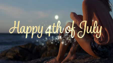 írott : Digital composite of Caucasian woman sitting by the beach during sunset while gold Happy 4th of July greeting appears in the foreground.