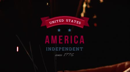 escrita : Digital animation of United States of America, Independent since 1776 text in banner zooming out in the screen while background shows lighted sparkles.