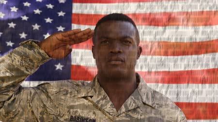 článek : Digital composite of American flag waving behind African American military man saluting while the written constitution of the United States moves in the foreground.