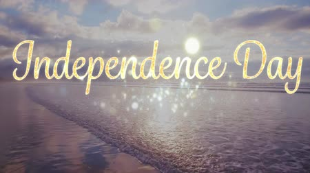 escrito : Digital animation of gold Independence day text with bokeh lights appearing in the screen with background of the sea with the sky during sunset