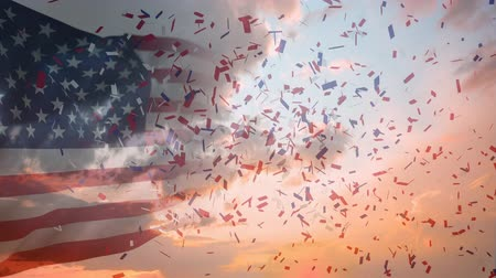 gurur : Digital animation of American flag waving while colorful confetti explodes and background shows the sky with clouds Stok Video