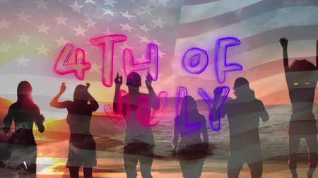 yazılı : Digital animation of 4th of July text appearing in the screen with American flag waving while background shows silhouette of diverse people jumping in the beach during sunset Stok Video