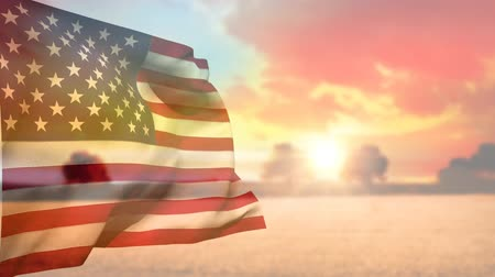národní vlajka : Digital animation of the American flag waving while background shows the sun setting over the sea