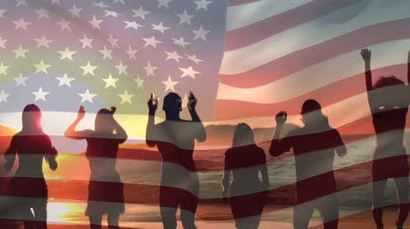 gurur : Digital composite of  silhouette of a group of diverse friends jumping at the beach during sunset while the American flag waves in the background