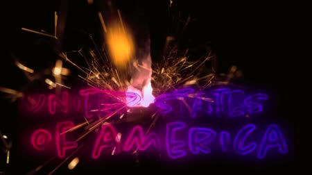 írott : Digital animation of a United States of America text in red and blue gradient appearing while a lighted sparkle flickers in the dark background for fourth of July