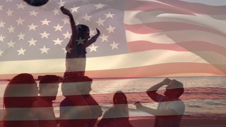 spangled : Digital composite of silhouette of a group of diverse friends celebrating at the beach with balloons during sunset while the American flag waves in the background for fourth of July.