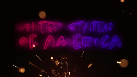 escrito : Digital animation of a United States of America text in red and blue gradient appearing while a lighted sparkle flickers in the dark background for fourth of July
