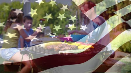 írott : Digital composite of a Caucasian family enjoying picnic and barbecue while an American flag waves in the background for fourth of July. Stock mozgókép