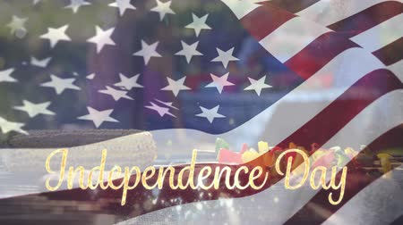 spangled : Digital animation of a gold Independence day text with bokeh lights while an American flag waves. Background shows barbecue on a fire grill outdoors with a diverse family having a picnic for fourth of July. Stock Footage