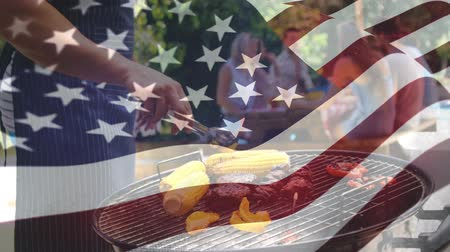 4分の1 : Digital composite of a man barbecuing while a diverse group of friends sit in a picnic table and an American flag waves in the background. 動画素材