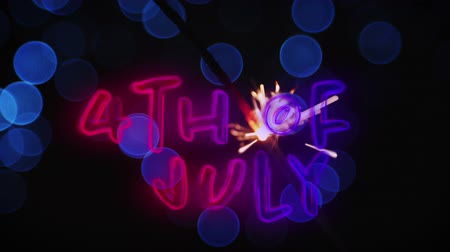 gurur : Digital animation of 4th of July text in red and blue gradient while blue bokeh and a lighted sparkle flickers in the dark background. Stok Video