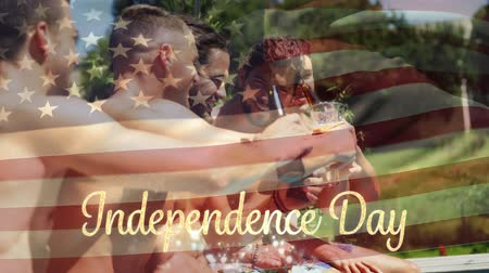 usa independence day : Digital composite of a group of diverse friends celebrating in a pool over drinks while the American flag waves behind a gold Independence Day text with bokeh. Stock Footage