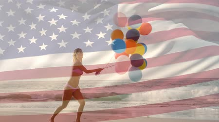 spangled : Digital composite of Caucasian woman holding balloons in the beach while an American flag waves in the background for fourth of July. Stock Footage
