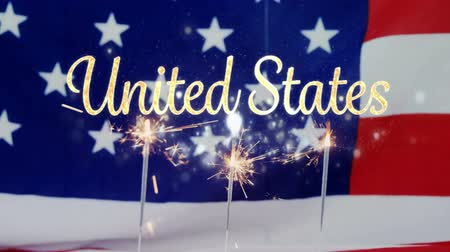 historia : Digital composite of an American flag behind cupcakes with lighted sparkles flicker and a gold United States text for fourth of July.