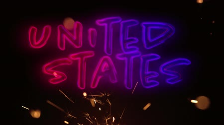 yazılı : Digital animation of a United States text in red and blue gradient while lighted sparkles flicker in the dark background for fourth of July. Stok Video