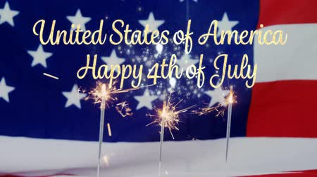 symbol : Digital composite of an American flag behind cupcakes with lighted sparkles flickering while a gold United States of America, Happy 4th of July text appears.