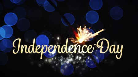 írott : Digital animation of a gold Independence Day text appearing with blue bokeh lights and a lighted sparkle flickers in the dark background for fourth of July.