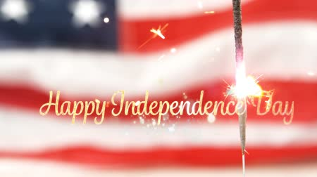 handschrift : Digital animation of gold Happy Independence Day text with bokeh lights and an American flag behind a lighted sparkle flickering in the background for fourth of July. Stockvideo